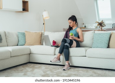 Shot of an attractive young woman taking a break while exercising at home