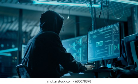 Shot from the Back to Hooded Hacker Breaking into Corporate Data Servers from His Underground Hideout. Place Has Dark Atmosphere, Multiple Displays, Cables Everywhere.