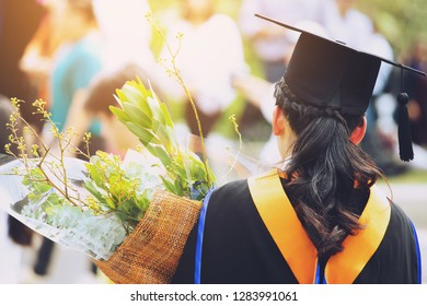 shot back side young female student in hand holding a bouquet of flowers  during commencement success graduates of the university, Concept education congratulation.