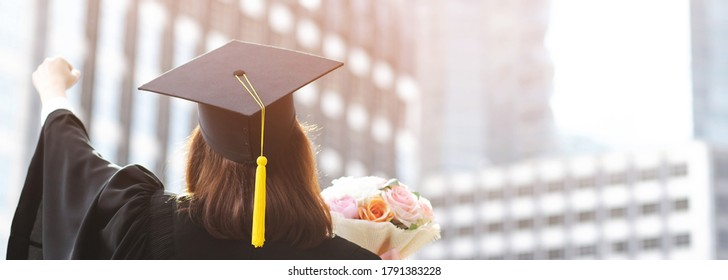 shot back side young female student in hand raising arms over fist thumb up and holding a bouquet of flowers during commencement success graduate of the university, Concept education congratulation.