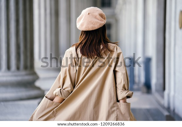 A shot of the back of a stylish Chinese Asian woman in an elegant French-inspired outfit (with a khaki trench coat and beret) in the corridor of a trendy building during the day.