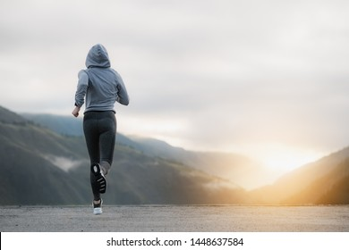Shot of a beautiful adult woman running at sunrise. Concept Sports and recreation.
