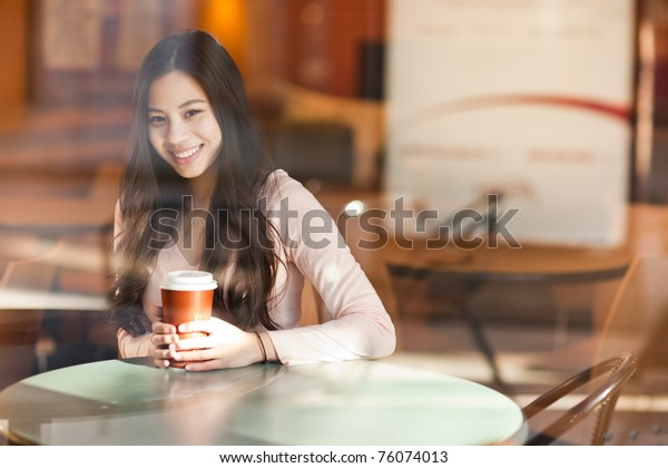 A shot of a beautiful asian woman drinking coffee in a cafe (shot through window)