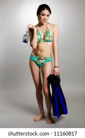A shot of a beautiful asian woman in swimsuit carrying snorkeling equipment