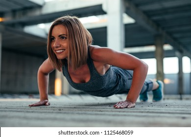 Shot of a beautiful athlete woman doing push ups in an abandoned building.