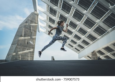 Shot of  beautiful athlete woman jumping doing cardio outdoor before running exercise. Attractive sporty girl training at sunny morning, healthy lifestyle