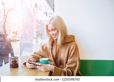 A shot of a beautiful blond student woman lokiing in smart phone, smile at a cafe.