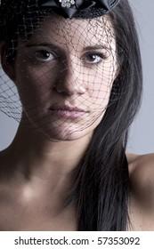 Shot of a Beautiful Brunette Girl In Veil against Grey