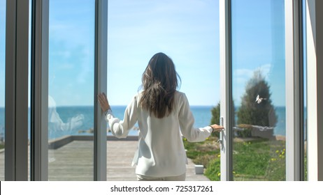 Shot of a Beautiful Brunette with Loose Hair Opening Doors of the Balcony and Walking onto Sunny Terrace with Seaside View. It's Cloudless Morning and She's Really Happy.