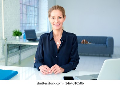 Shot of beautiful businesswoman looking at camera and smiling while sitting at desk in the office.