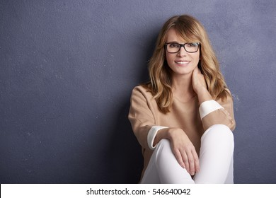 Shot of a beautiful cheerful woman looking at camera and smiling while sitting in front of  a grey wall.