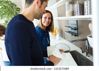 Shot of beautiful couple having fun and cleaning the kitchen utensils at home.