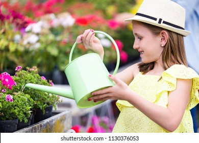 Shot of beautiful girl watering the plants in the greenhouse.