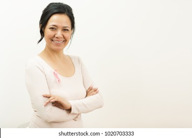 Shot of a beautiful mature Asian woman smiling to the camera wearing pink ribbon breast cancer awareness symbol on her shirt copyspace medicine healthcare consciousness prevention survivor confidence.