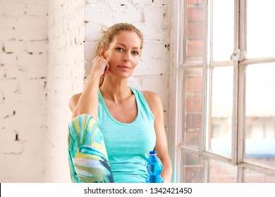 Shot of a beautiful mature woman relaxing after practicing yoga in fitness studio while looking at camera and smiling.
