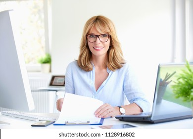 Shot of a beautiful middle aged businesswoman sitting at office desk and doing some paperwork while working computer and laptop. Multitasking.