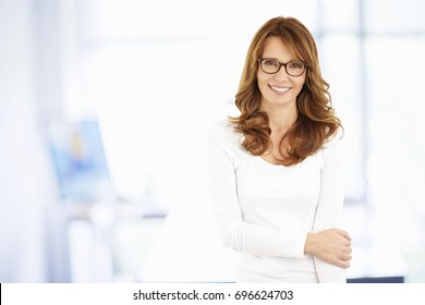 Shot of a beautiful middle aged professional woman standing at the office while looking at camera and smiling.