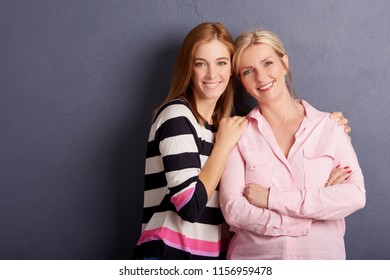 Shot of a beautiful mother and daughter standing at grey wall and enjoy each other's company. Copy space.