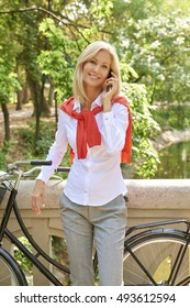 Shot of a beautiful smiling woman talking on her mobile phone while standing in the park with her bicycle.