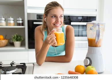 Shot of beautiful sporty young woman looking sideways and drinking vegetable detox juice in the kitchen at home.