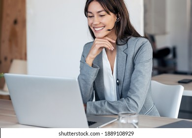 Shot of beautiful young business woman making video call with computer while talking with earphone sitting in modern startup office.
