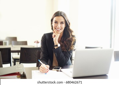 Shot of a beautiful young businesswoman doing some paperwork while sitting at office desk in front of laptop.