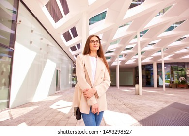 Shot of beautiful young businesswoman standing at office building and waiting for somebody.