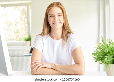 Shot of beautiful young businesswoman with toothy smile sitting at computer at the modern office.