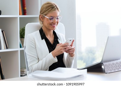 Shot of beautiful young businesswoman using her mobile phone in the office.