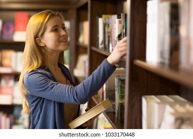 Shot of a beautiful young cheerful female student picking books from the shelf at the college library copyspace campus high school educational university assignment project study research.