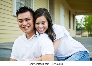A shot of a beautiful young couple sitting on the porch of their house