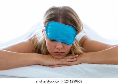 Shot of beautiful young exhausted woman with sleep mask suffering insomnia trying to sleep over white blackground.