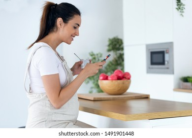 Shot of beautiful young pregnant woman using her mobile phone while eating an ice cream in the kitchen at home.