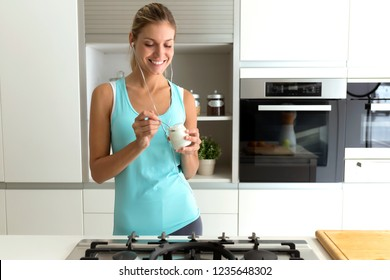 Shot of beautiful young sporty woman listening to music and eating yogurt in the kitchen at home.