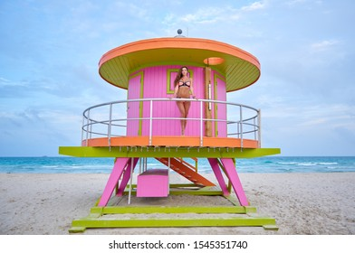 Shot of a beautiful young woman in a bikini standing by a lifeguard hut at the beach