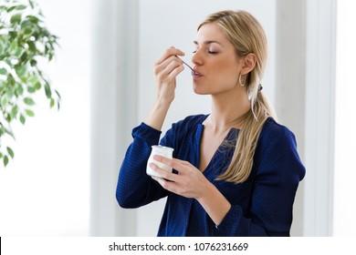Shot of beautiful young woman eating yogurt at home.