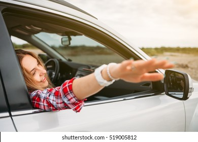 Shot of beautiful young woman enjoying road trip on a summer day. Excited young Female raising her hand out of the car.