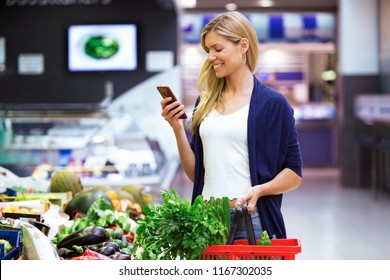 Shot of beautiful young woman looking shopping list on mobile phone while buying fresh vegetables in the market.