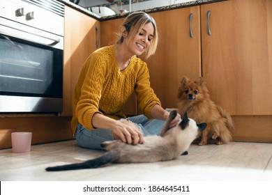 家のキッチンの床に座って可愛い動物と遊んでいる美しい若い女性の写真。