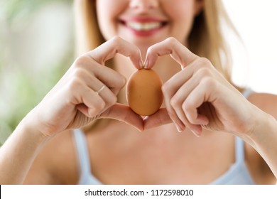 Shot of beautiful young woman showing brown chicken egg with hands in a heart shape at home.