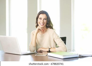 Shot of a beautiful young woman sitting at desk and working on laptop from home.