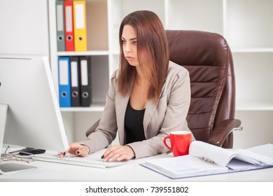 Shot of beautiful young woman sitting at her work desk going through some documents. European business woman working in modern office.