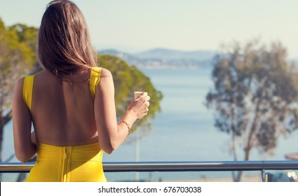 Shot of beautiful young woman standing on the balcony with beverage and looking at the view