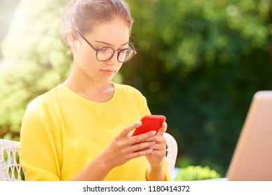 Shot of beautiful young woman text messaging while sitting outdoors in front of laptop and working on presentation.