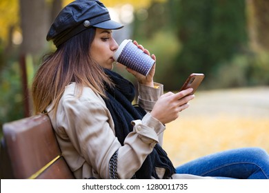 Shot of beautiful young woman using her mobile phone while drinking coffee and sitting in a bench in the street.