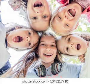 Shot from below of happy smiling little girls standing in circle