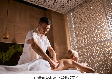 Shot from below. Young shy man in round glasses massaging charming blonde girl in modern wellness center, body care, skin care, wellness, well being concept