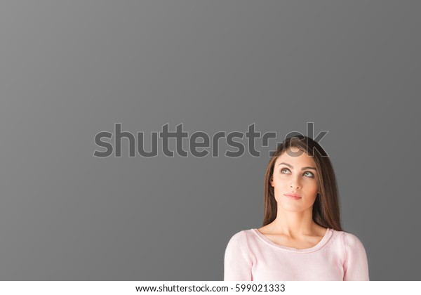 Shot with big copy space of a serious young woman looking up