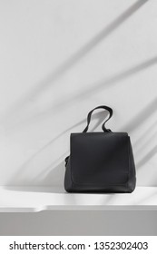 Shot of a black leather backpack with flap top and handle, isolated against the white platform against light gray wall. There is a stripy shadow on the background. Fashionable women's fashion item.