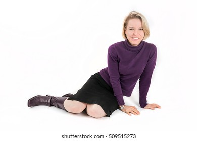 Shot of a blonde woman lying and smiling in front of a white background